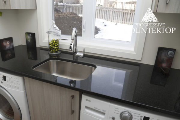 Modern laundry room with new countertop by Progressive Countertop